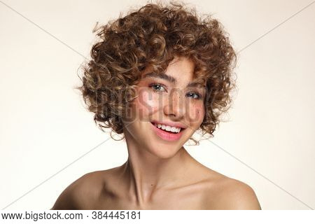 Portrait of smiling beautiful freckled girl with curly hair