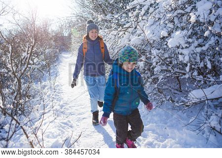 The Child Runs Away From Mom. A Woman Walks With A Child In A Winter Park. The Boy Spends Time With