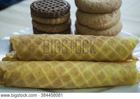 Waffle Rolls And Cookies On A White Plate For Tea, Breakfast. Waffles In Front. Composition On A Woo