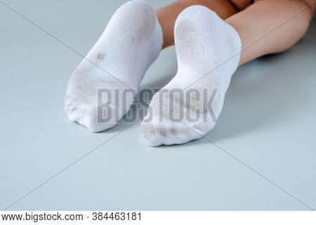 Pair Of Child Feet In Dirty Stained White Socks. Dirty Socks Pair Of Child Feet In Dirty Stained Whi