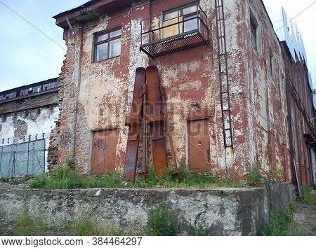 Huge Skis Near The Facade Of The Factory Floor. Skis And Ski Poles Are Made Of Rusting Metal And Lea
