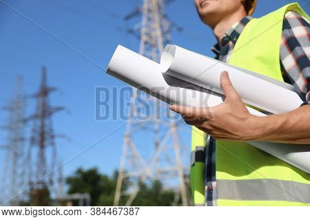 Professional Electrician With Draftings Near High Voltage Tower, Closeup