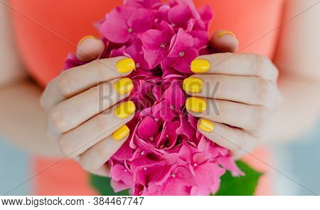 Women with manicured nails in yellow holding a flower