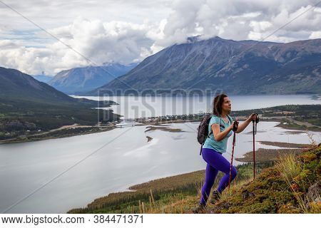 Adventurous Girl Hiking Up The Nares Mountain During A Cloudy And Sunny Evening. Taken At Carcross,