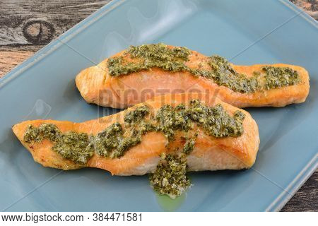 Two Baked Salmon Fish Fillets With Basil Pesto Sauce On Blue Serving Platter On Table
