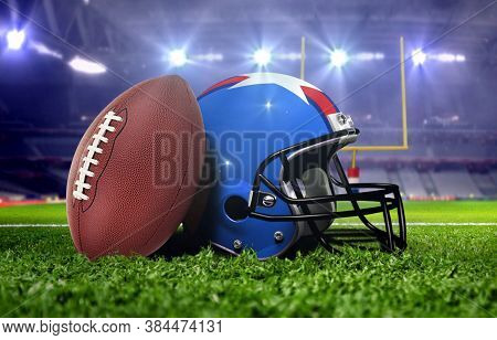 American Football And Helmet On The Field With Goal Posts In The Background Under Bright Spot Lights