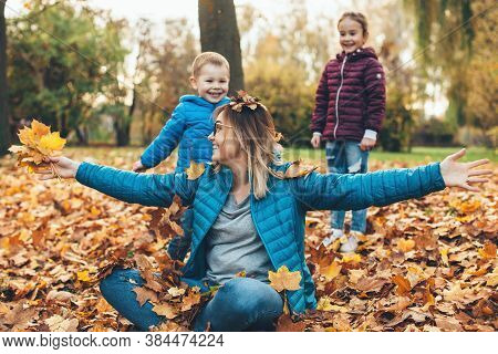 Caucasian Mother With Glasses Is Playing In Leaves With Her Son And Daughter During A Walk In Park