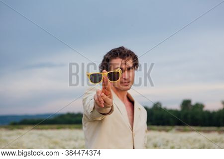 Tall Handsome Man Standing In Camomile Flowers Field And Posing With Yellow Sunglasses