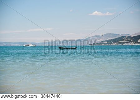 Empty Wooden Boat With No People In Bay Sea With Sky And Mountain Background, Horizontal Stock Photo