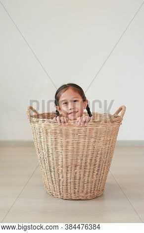 Smiling Asian Little Girl Sitting In Rattan Basket In Room At Home