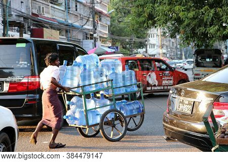 Yangon, Myanmar, Feb 20, 2019: Myanmese Worker Man Pushing The Three Wheel Of Water Tanker Barrow On