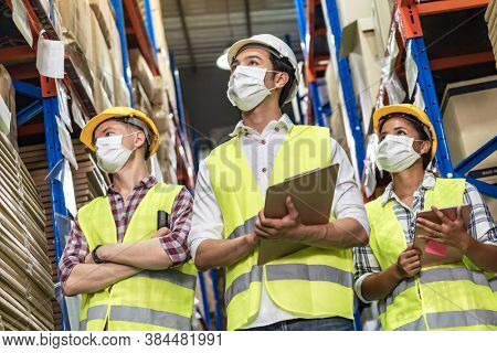 Portrait of Interracial group Asian African and Caucasian with clipboard and barcode scanner wear face mask to prevent COVID-19 coronavirus infection in distribution center. Business teamwork concept.