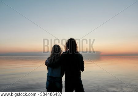 Silhouetted Couple Embracing While Watching Beautiful Sunset On The River Together, Back View, Horiz