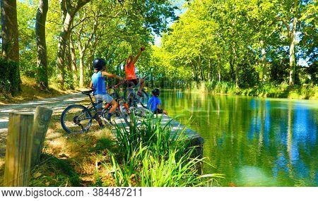 happy family biking along of river- Canal du Midi-France