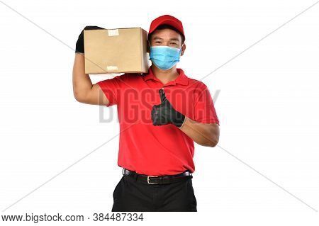 Happy Young Asian Delivery Man In Red Uniform, Medical Face Mask, Protective Gloves Carry Cardboard