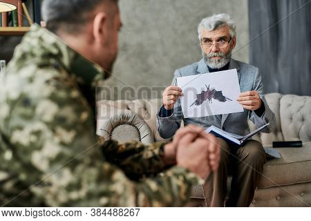 Mature Psychologist Holding Picture With Ink Stain, Rorschach Inkblot In Front Of Military Man Durin