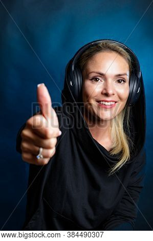 Blonde Woman With Headphones. Smiling, Looking At The Camera. Photography In The Studio, Dark Backgr