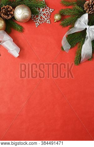 Christmas Red Background With Fir And Decor. Top View With Space For Copy.