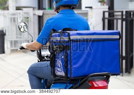 Delivery Man Wearing Blue Uniform Riding Motorcycle And Delivery Box. Motorbike Delivering Food Or P