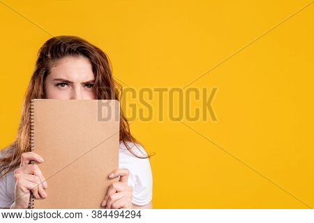 Skeptic Student Portrait. Exam Stress. Worried Woman Hiding Face Behind Beige Blank Notebook Isolate
