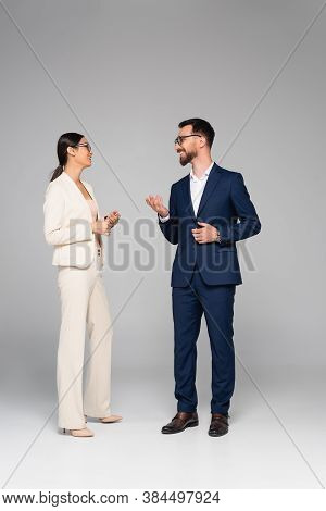 Full Length View Of Interracial Business Colleagues In Formal Wear Talking And Gesturing On Grey