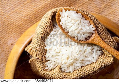 Top View Of Jasmine Rice In A Wooden Spoon And In A Sack Put In A  Wooden Bowl On Sackcloth