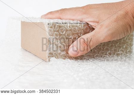 Hand Of Man Hold Bubbles Covering The Box By Bubble Wrap For Protection Product Cracked  Or Insuranc