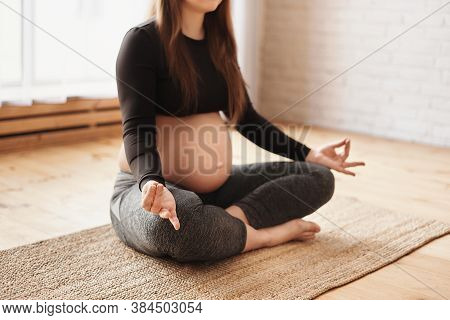 Meditating On Maternity. Close-up Of Pregnant Woman Meditating While Sitting In Lotus Position. Pren