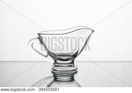 Empty Clear Glass Gravy Boat Isolated On A White Background