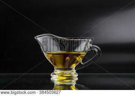 Clove Oil In A Glass Sauceboat On A Black Background. Cloves In A Gravy Boat
