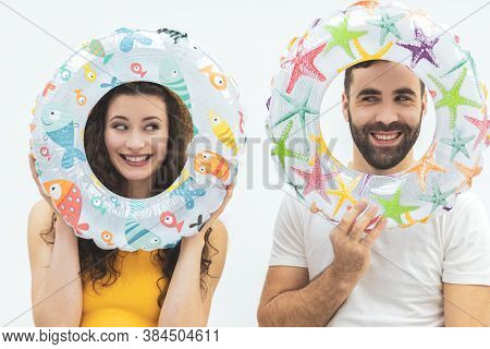 Beautiful Young Couple Holding Life Preservers Over Their Faces.