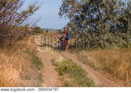 Father And Daughter With Suitcase Walking Off-road On Nature Lanscape Back View. Little Blonde Girl