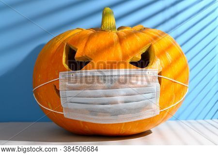 New Normal Concept. Glowing Halloween Pumpkin In A Protective Medical Mask On A Pastel Blue Backgrou