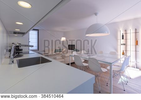 Modern kitchen with white worktop and gray sink. Large glass table, designer chairs, comfortable leather sofas and a bookcase with wine bottles and LEDs. Nobody inside