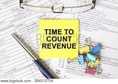 Yellow Sticker With Text Time To Count Revenue. Next To It Is A Blue Pen With Colored Stationery Cli