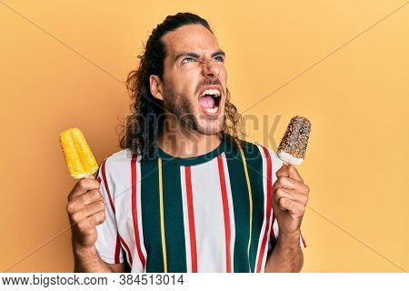 Young handsome man with long hair eating two ice cream angry and mad screaming frustrated and furious, shouting with anger looking up.