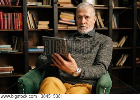 Portrait Of Confident Bearded Gray-haired Mature Adult Male Holding Digital Tablet In Hand Sitting A