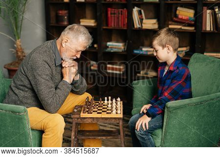 Thoughtful Beard Grandpa Playing Chess With Grandson, Thinking About Next Step In Chess Game Sitting