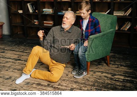 Stylish Bearded Grandfather With His Lovely Grandson Enjoy Memories Watching Family Photo Album Sitt