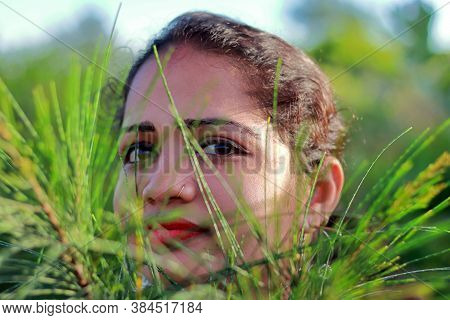 The Face Of A Beautiful Indian Young Woman Behind The Leaves Of Trees, Beauty Woman Face Portrait, C