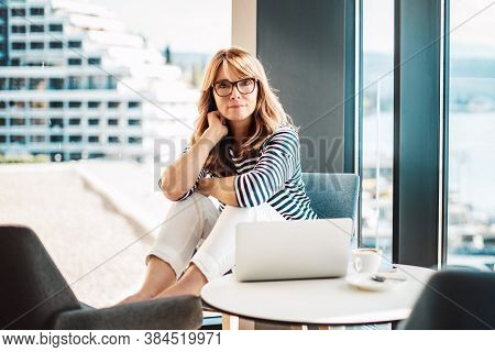 Shot Of Middle Aged Smiling Woman Using Laptop While Sitting In Her Modern Home And Working Online.