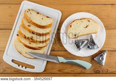 Slices Of Bread With Raisin On Cutting Board, Kitchen Knife, Slice Of Bread And Slices Of Creamy Che