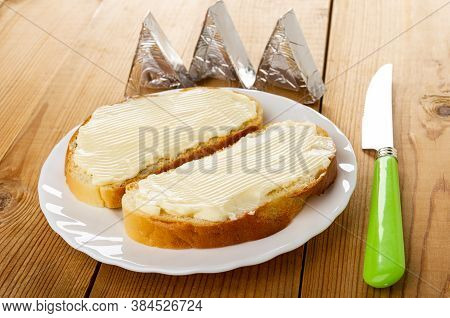 Cheese In Foil, White Plate With Sandwiches With Cream Cheese, Table Knife On Wooden Table