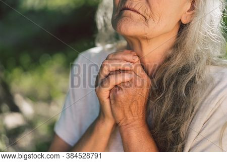The Gray-haired Grandmother Is Praying In Outdoors. Faith, Spirituality And Religion Concept. Peace,