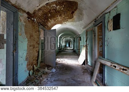 Corridor With Open Doors In An Old Abandoned Psychiatric Hospital