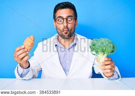 Young hispanic man as nutritionist doctor holding croissant and broccoli making fish face with mouth and squinting eyes, crazy and comical.