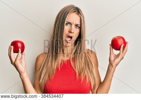 Young blonde woman holding red apples in shock face, looking skeptical and sarcastic, surprised with open mouth