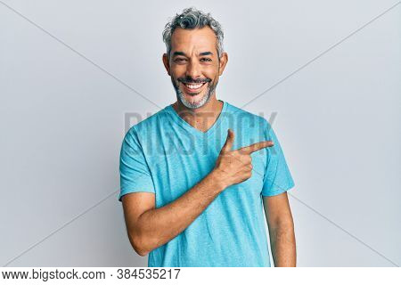 Middle age grey-haired man wearing casual clothes cheerful with a smile of face pointing with hand and finger up to the side with happy and natural expression on face
