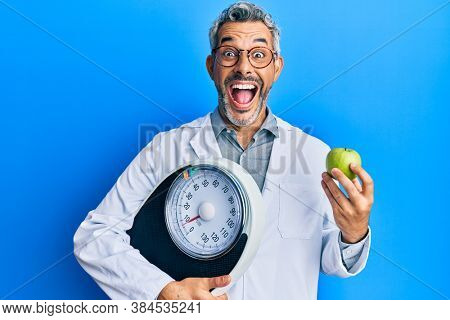 Middle age grey-haired man as nutritionist doctor holding weighing machine and green apple celebrating crazy and amazed for success with open eyes screaming excited.