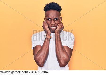 Young african american man wearing casual clothes covering ears with fingers with annoyed expression for the noise of loud music. deaf concept.